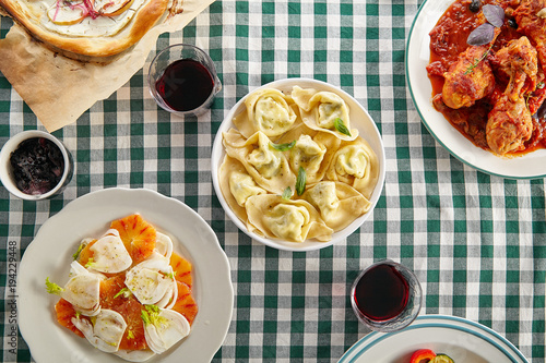 Fotobehang Toscane Traditional italian tuscan family dinner with homemade pasta and chicken cacciatore, focaccia and salad served on a table covered with green checkered tablecloth