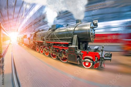 Stary retro pociąg lokomotywy z klubami pary i dymu dociera do stacji pasażerskiej pod dachem.
