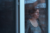 Depressed woman standing by the window and looking outside - 194237673