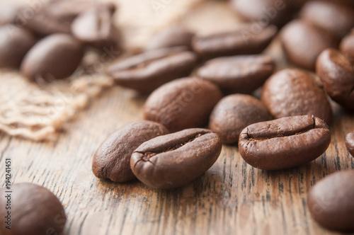 Tuinposter Koffiebonen grains de café et toile de jutte sur table en bois