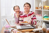 Mother and daughter baking cookies, girl eat cookie, home kitchen interior, healthy food concept - 194244096