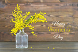 Happy Women's Day card with mimosa flowers in the bottle