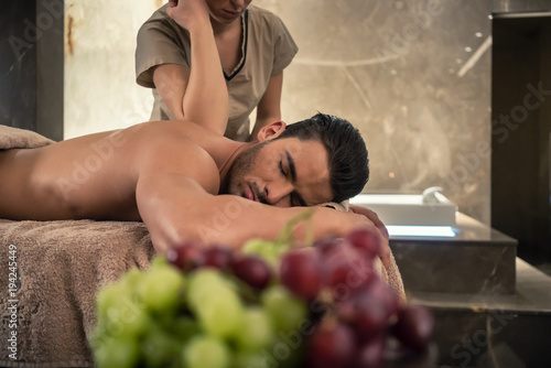 Leinwanddruck Bild Young man lying down during traditional acupressure procedure of Thai massage at luxury spa and wellness center