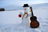 Christmas  snowman  with baubles, hat and old guitar