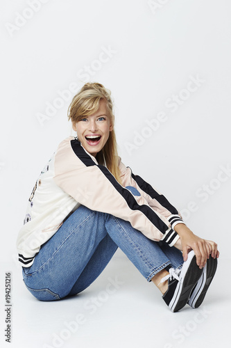 Fototapeta Excited varsity girl sitting in studio, portrait