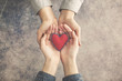 Man and woman hands together with red heart