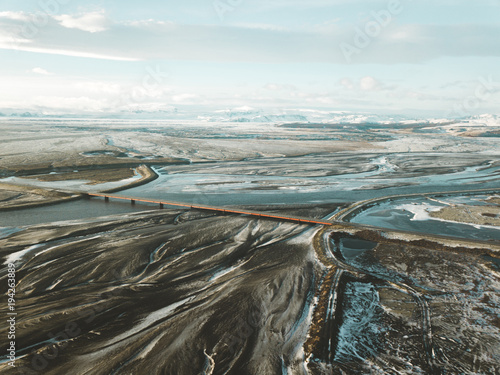 Aluminium Wit Aerial view of Iceland winter texture, frozen glacier river, bridge, road, delta of river, volcano, black sand, mountains, abstract landscape
