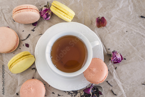 Plexiglas Macarons french macaroons, white cup of tea and rose petals on crumpled paper with copy space