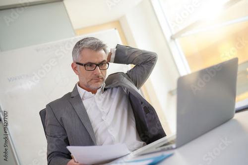 Fototapeta Businessman in office working on laptop