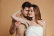 Young shirtless man holding and hugging his woman isolated