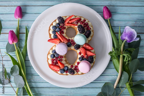 Cake in shape of number 8 decorated with berries and flowers tulips. Dessert for women's day on the eighth of March