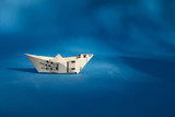 Paper boat made of musical score sheet in blue background