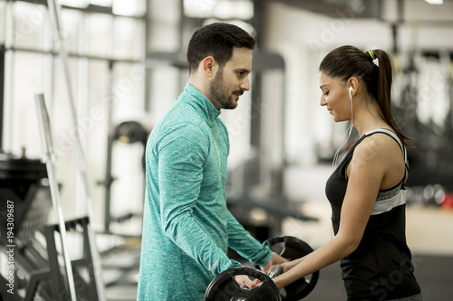 Fotobehang Fitness Young woman with personal trainer in gym