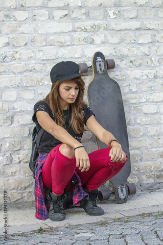 Aluminium Skateboard Young urban girl kneel in front of brick wall with skateboard beside her