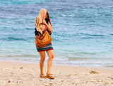 A chilly woman walking and shaking on the beach. End of summer with bad weather. - 194317254