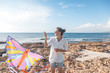 Beautiful happy young woman girl launches a kite at the seashore, sunshine vacation and joy concept