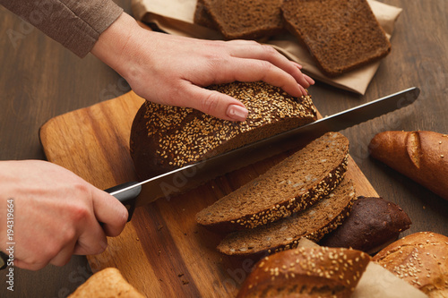 Cutting bread on wooden board top view - 194319664