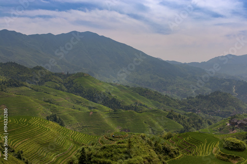 Fotobehang Rijstvelden View of the Longsheng Rice Terraces near the of the Dazhai village in the province of Guangxi, in China, with a female farmer working the land;