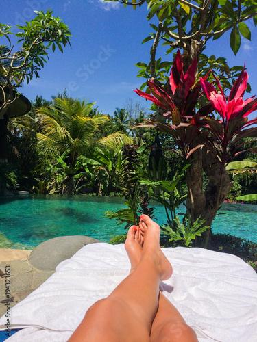 Fotobehang Bali Young woman relaxing by the pool in Ubud, Bali