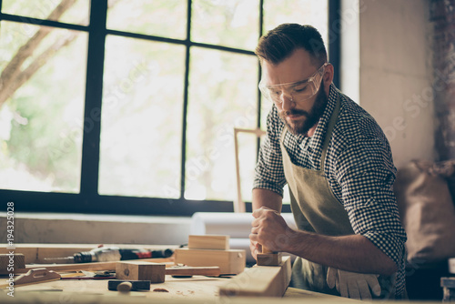 Confident professional busy hardworking bearded handsome serious wearing checkered casual shirt apron and protective goggles is aligning the surface of wooden plank with a plane near window - 194325028