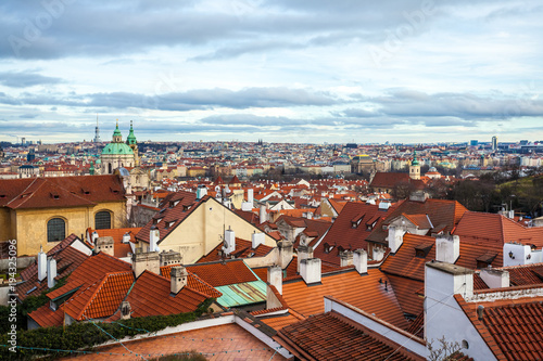 In de dag Praag View of Prague over houses with red roofs. Amazing view from above at old historical quarter. Prague, Czech Republic. Prague is famous and popular travel destination city