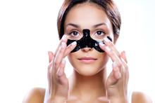 Beautiful Woman Applying Coal Mask Sticker