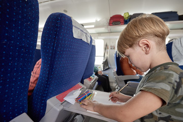 Boy traveling by train. Young boy sitting in train and drawing during trip