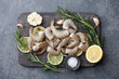 Cooking fresh raw tiger prawns with rosemary, lemon, lime, garlic and spices on stone countertop, top view