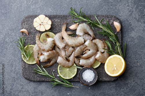 Aluminium Tijger Cooking fresh raw tiger prawns with rosemary, lemon, lime, garlic and spices on stone countertop, top view