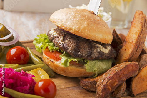 hamburger burger  grilled with fried potatoes and pickles on a wooden board