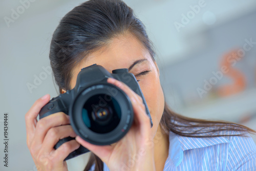 a girl taking a photo with a dslr camera