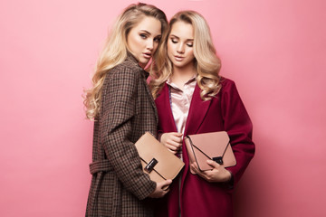Two sweet young women posing in nice clothes, coat, handbag. Sisters, twins. Spring fashion photo.