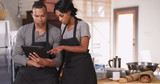 Small business owner showing employee new plan on tablet computer. African American woman running bakery with husband - 194365876