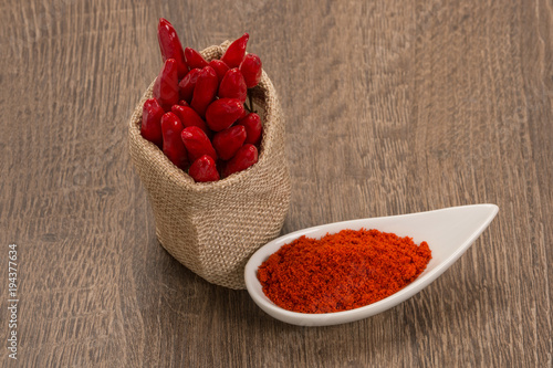 Tuinposter Hot chili peppers Red pepper powder over wood background