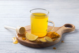 Energy tonic drink with turmeric, ginger, lemon and honey on a wooden board, selective focus - 194379820