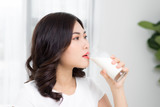 Beautiful asian girl drinking a glass of milk. - 194381293