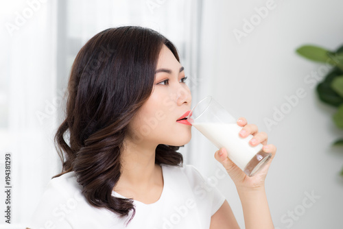 Fototapeta Beautiful asian girl drinking a glass of milk.