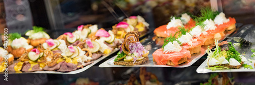 Danish smorrebrod traditional open sandwich at Copenhagen food market store. Selection of fish sandwiches on display with seafood and meat, smoked salmon.