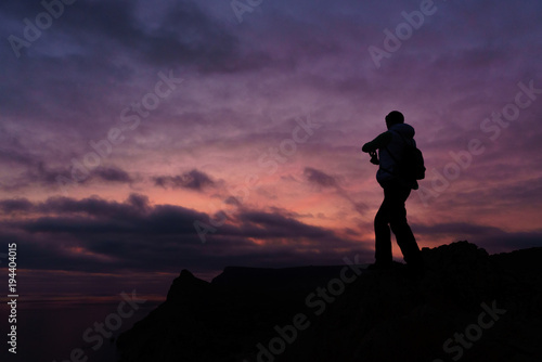 Aluminium Aubergine Silhouette of a person taking photo of a sunset with purple background