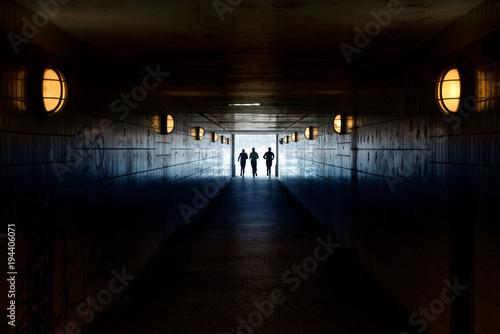 Trzy osoby uciekające przez tunel