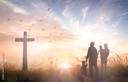 Family worship concept: Silhouette people looking for the cross on autumn sunrise background