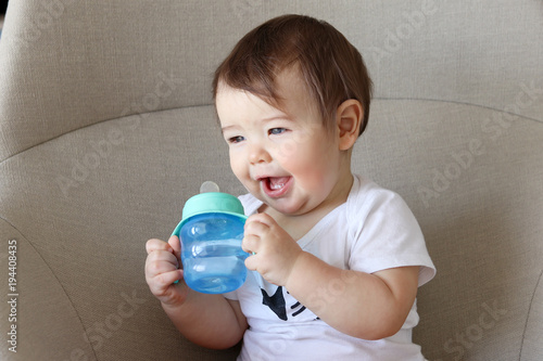 Little baby smiling happily and holding bottle with water in his hands, drinking water