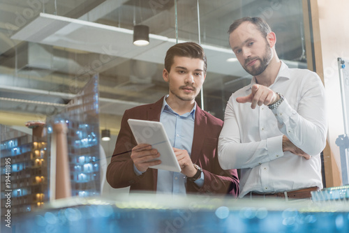 architects with tablet in front of building models
