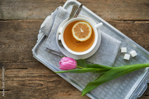 Fototapeta Pink tulip and a cup of green tea with lemon on a tray