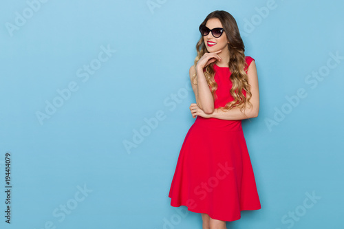 Bautiful Woman In Red Dress And Sunglasses Is Looking Away