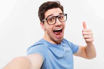 Joyful man in t-shirt and eyeglasses making selfie