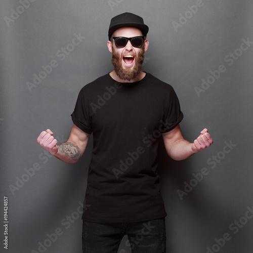 Modniś przystojny samiec model z brodą jest ubranym czarną pustą koszulkę z przestrzenią dla twój loga lub projekta nad szarym tłem