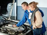 Automechaniker mit Kundin in der Werkstatt