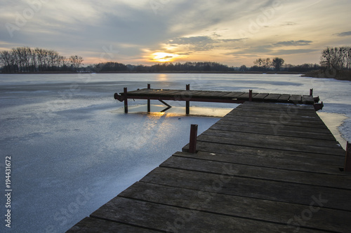 Aluminium Pier Wooden jetty and frozen lake at sunset