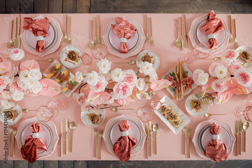 Festive table decor. In pastel pink colors with golden cutlery. With different natural colors roses, peonies, anthurium. Luxury wedding, party, birthday. View from above © 072Y